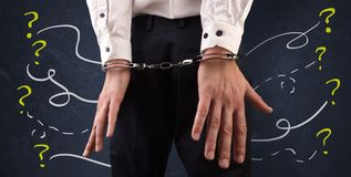 Close prisoner hand with questions around. Now arrested men with handcuffs and chalk drawn question signs and lines around Stock Photo