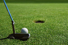 A Close Putt with lots of Copy Space. A golfer is achingly close to the cup. Focus is on the golf club and ball with the hole slightly out of focus in the Stock Photography