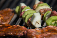 Close on raw meat with fruits on the grill Stock Photo