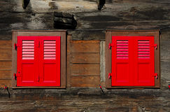 Close red shutters. Of a block house made of dark oak wood Royalty Free Stock Image