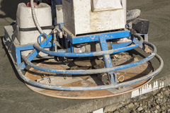 Close of ride on power trowel on fresh concrete Royalty Free Stock Images