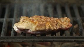 Close the seasoned beef steak on the grid through the haze and smoke of heat - Slow chamber, restaurant dish, delicacy. A large piece of steak 4k stock video
