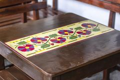 Close shoot of wooden table with flower ornamentation royalty free stock photo