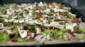 Close shot of adding the mushrooms over the pizza. Adding various pizza ingredients all over the dough stock video