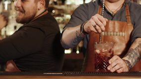 Close shot on the barmen`s hands, companions prepare alcoholic cocktails in the bar. A close shot at the barmen`s hands, men prepare cocktails, one of the bar stock video footage