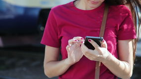 Close shot of beautiful woman using smartphone at train station stock video