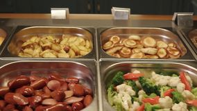 Close up shot of the buffet with a variety of food, containers rhe products. Close shot at the buffet in the hotel, on the table are cutlets, steamed vegetables stock video footage