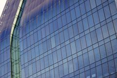 Close shot of a curved blue glass window wall of a modern and elegant corporative building. Some office paraphernalia can be distinguished through the glass royalty free stock photo