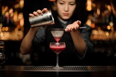 Close shot of female bartender preparing cocktail with shaker and sieve. Close shot of beautiful female bartender preparing alcohol cocktail with a steel shaker stock photos