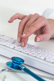 Close shot of a female doctor taping on keybord Royalty Free Stock Images