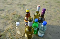 Bottles on sea beach. Close shot of group of opened and unopened glass and plastic bottles of alcoholic drinks and non-alcoholic beverages standing on sand stock photo