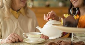 Hands of young woman with white china teapot pouring tea into cup of her senior mother. Close Shot Of Hands Of A Daughter Who Pours Tea From Porcelain Teapot royalty free stock image