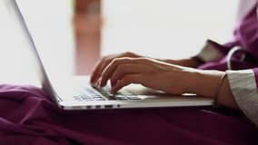 A close shot at the hands of a woman who quickly prints text on the laptop keyboard, the ladies are working in the stock video footage