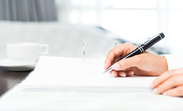 Close shot of a human hand writing something on the paper Royalty Free Stock Images