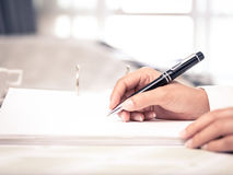 Close shot of a human hand writing something on the paper Stock Photo