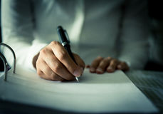 Close shot of a human hand writing something on the paper Stock Photos