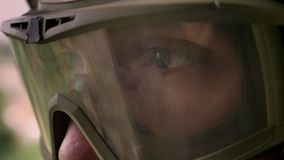 Close shot of man`s eyes in protective glasses looking sideways, military stock footage