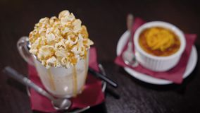 A close shot at a milkshake with creamy foam and caramel or vanilla flavor, on the saucer is a tube, next to the sweet. A close shot at a milkshake or frappa stock footage