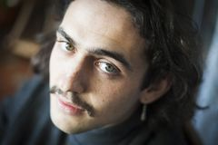 Long haired young man with moustache and ear ring portrait stock photos