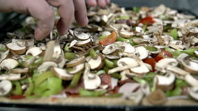 Close shot of rearranging the vegetables around the pizza stock video footage