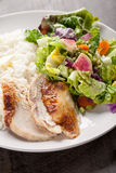 Close shot of salad and chicken on dark wood. Italian salad with rotisserie chicken and white rice close shot Royalty Free Stock Photography