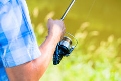 Close shot of sport fisherman reeling in line on fishing rod stock image