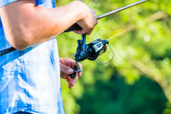 Close shot of sport fisherman reeling in line on fishing rod stock photos