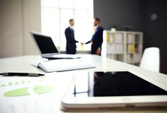 Close-shot of a tablet computer with businessmen handshaking Stock Photo