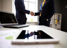Close-shot of a tablet computer with businessmen handshaking Royalty Free Stock Images