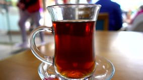 Close shot of traditional Turkish tea glass in a restaurant on table with people in the background. Close shot of traditional Turkish tea glass in a restaurant stock footage