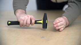 Close shot of using a hammer to nail down a nail. Two men are assembling new furniture in freshly painted room. They use compact cordless drill-driver, hammer stock video