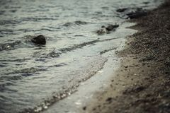 A close shot of water on a lake shore, with details of bubbles and little stones on the sand.  Royalty Free Stock Image