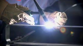 Close shot of welding some metal part. Man using welding machine to fix the door handle stock video footage