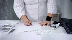 A close shot at a woman`s hands, who looks like a seamstress, the master paints a sketch of a collection of clothes on stock video