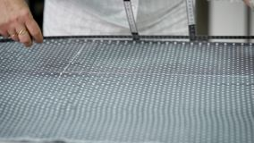 Close shot of a woman`s hands, who makes grades using chalk on a fabric in order then to cut it and make a dress stock video footage