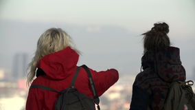 Close shot of women trying to find familiar place in great view. Two young women stop for a magnificient view over Ljubljana city stock video footage