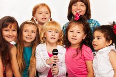 Close shots of kids singing. Close-up shoot of a large group of five happy little kids, boys and girls, singing together sitting to microphone on the coach at Royalty Free Stock Photography