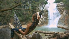 Girl Rests in Hammock Hung over Rocks by Waterfall. Close side picture blond girl rests lying in hammock hung above rocks against pictorial foamy waterfall stock footage