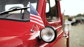 Close side view of red pickup truck with small American flag waving in slo-mo slow motion.  stock footage