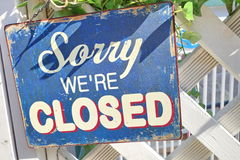 'Close' Sign. A sign written 'Sorry, we're closed' hanging on a white fence Royalty Free Stock Photos