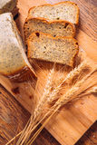 Close slice of fresh bread with poppy seeds and wheat ears on wooden background Stock Photography