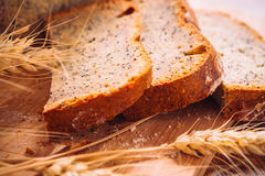 Close slice of fresh bread with poppy seeds and wheat ears on wooden background Royalty Free Stock Photos