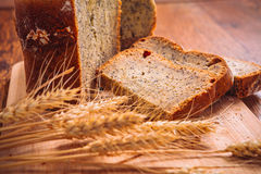Close slice of fresh bread with poppy seeds and wheat ears on wooden background Stock Photo