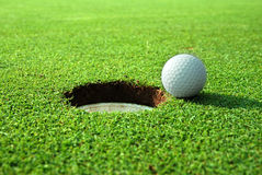 Close to the goal!. Close up of a golf ball close to the hole Stock Photography