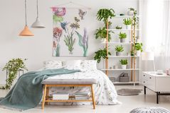 Close to nature bright bedroom interior with a bed covered with white sheets and marine blanket. Green plants on shelves next to t stock image