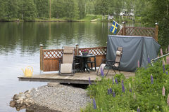 Close to the river. Some chairs and a table close to the river and a swedish flag Royalty Free Stock Image