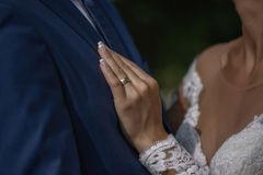 Close together bride and groom, bride holding left hand on groom`s chest in a gesture of love and commitment. Stock Photos