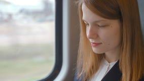 Close up à cara da senhora nova do negócio ao datilografar no portátil no trem video estoque