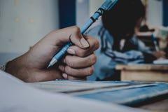Close up à mão da pena de terra arrendada do estudante e ao exame da tomada no classr Foto de Stock