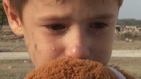 Close-up órfão pequeno sujo do menino que grita e filme